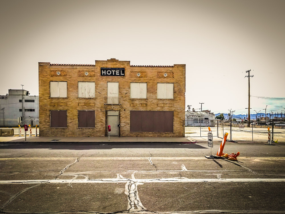 Leftover hotel amidst a parking lot.